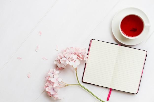 Diario con taza de té y flores.