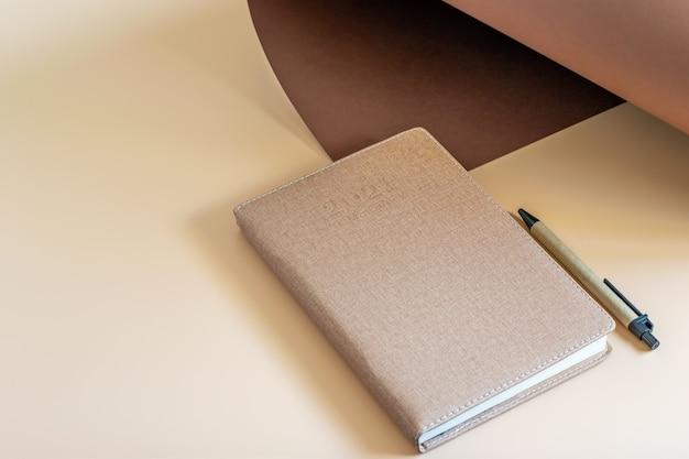 Diario de tiempo, un bolígrafo y una hoja de papel sobre el fondo beige. vea en ángulo, plantilla de maqueta que ofrece mostrar su texto o logotipo.