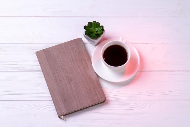 Diario de vista superior con taza de café o té y planta. fondo de escritorio blanco.