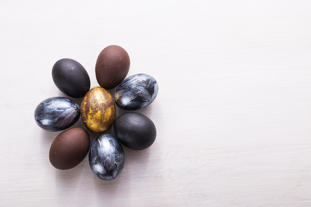 Días de fiesta, tradiciones y concepto de pascua - huevos de pascua elegantes oscuros en el fondo de madera blanco con el copyspace.