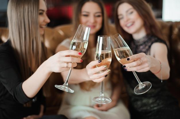 Días de fiesta, vida nocturna, despedida de soltera y concepto de la gente - mujeres sonrientes con los vidrios del champán.