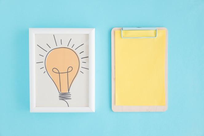 Dibujado a mano bombilla marco y portapapeles con papel amarillo