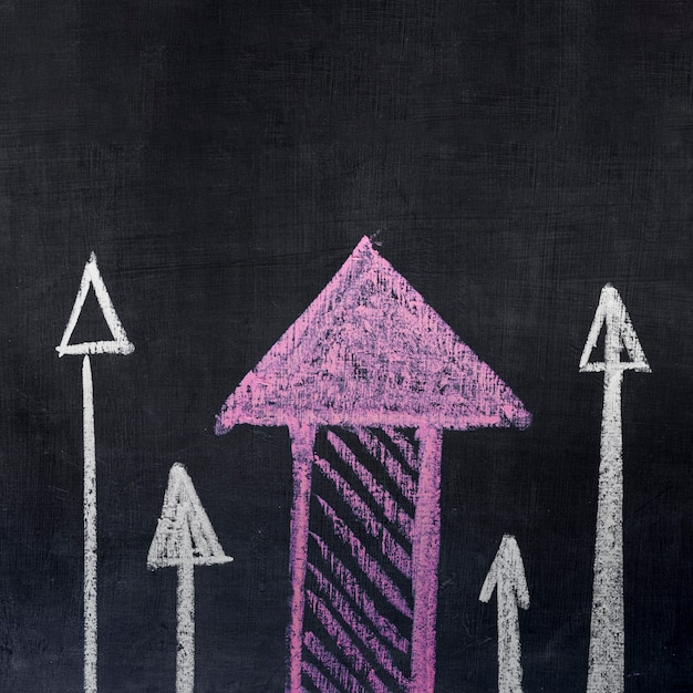 Dibujado flechas apuntando hacia arriba sobre fondo de pizarra