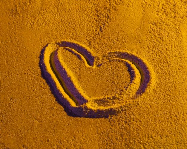 Dibujado en forma de corazón sobre textura de arena