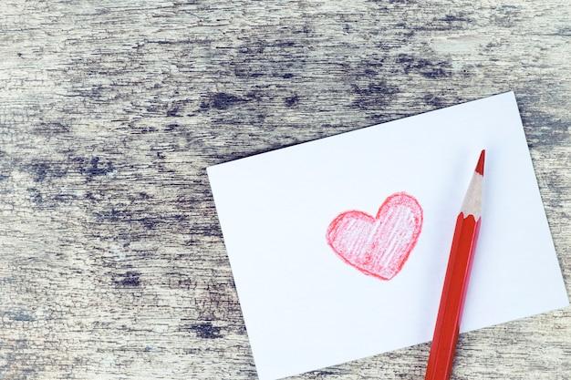 Dibujado a mano de corazón rojo tarjeta de san valentín sobre fondo de madera oxidado