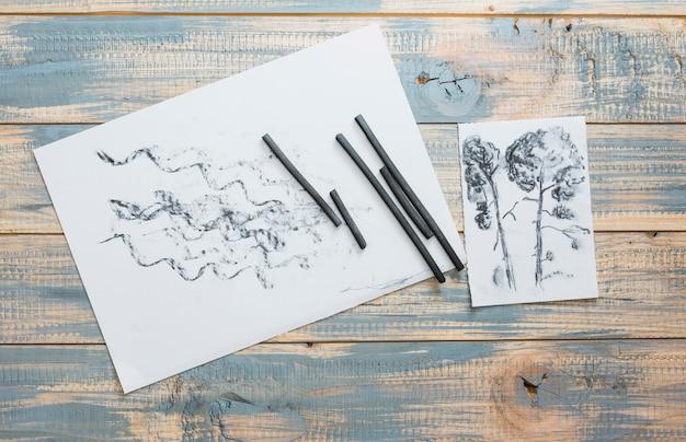 Dibujado papel y materiales de arte carboncillo en mesa de madera