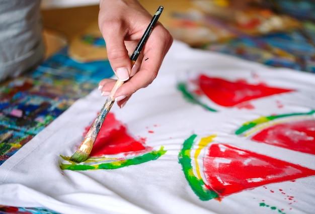 Dibujando en la ropa. niña dibuja en una camiseta blanca.