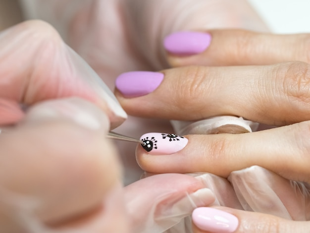 Dibujando en tus uñas. manicura creativa con coronavirus pintado en las uñas, enfoque suave, primer plano