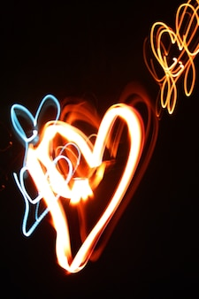 Dibuje chispitas de fuego de corazón en la noche oscura para el amor y el día de san valentín y la celebración