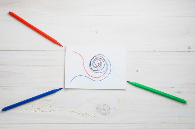 Dibujo abstracto sobre papel blanco con rojo; rotulador verde y azul sobre escritorio de madera