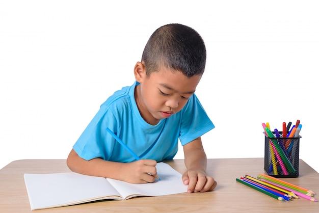 Dibujo alegre lindo del niño usando el lápiz del color mientras que se sienta en la tabla aislada en el fondo blanco