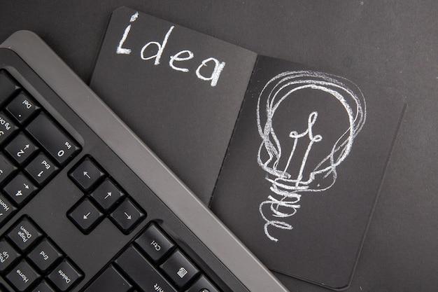 Dibujo de bombilla idealight de vista superior en el teclado de bloc de notas negro en la oscuridad