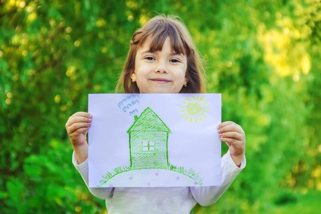 Dibujo de una casa verde en manos de un niño.