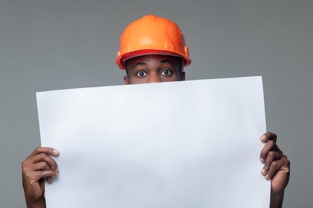 Dibujo de construcción. hombre con casco naranja brillante sosteniendo una gran hoja de papel blanco al nivel de su rostro, solo los ojos son visibles
