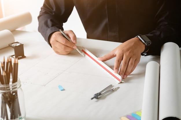 Dibujo cosechado de la arquitectura del tiro en el papel de modelo con los divisores en las manos.