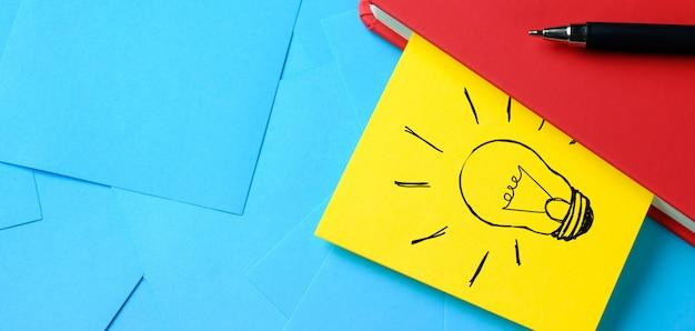 Dibujo creativo de una bombilla en una pegatina amarilla adjunta a un bloc de notas rojo. hay una pluma al lado. el concepto de nuevas ideas, innovaciones, soluciones a problemas. bandera