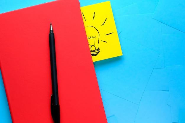 Dibujo creativo de una bombilla en una pegatina amarilla adjunta a un bloc de notas rojo. hay una pluma al lado. el concepto de nuevas ideas, innovaciones, soluciones a problemas.