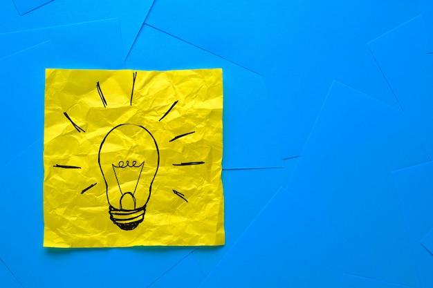 Dibujo creativo de una bombilla en una pegatina arrugada amarilla, sobre un fondo de pegatinas azules. el concepto de nuevas ideas, innovaciones y soluciones a los problemas.