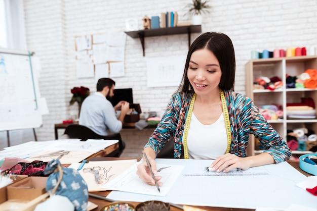 Dibujo de diseñador de moda con regla om papel.