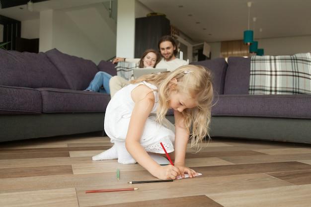 Dibujo lindo de la hija de la muchacha con los lápices coloreados que juegan en casa