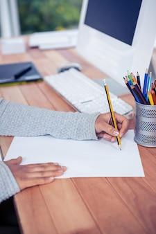 Dibujo de la mano de la mujer con el lápiz en la hoja blanca en oficina