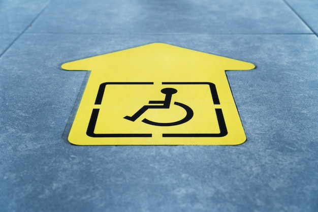Un dibujo de una silla de ruedas sobre una flecha amarilla pegada al azulejo de la sala de espera.