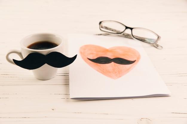 Dibujo sobre papel junto a taza de bebida y gafas.
