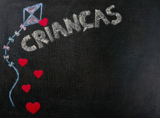 Dibujo sobre papel de lija. crianças (portugués) escrito en pizarra y corazones. copia espacio de fondo.