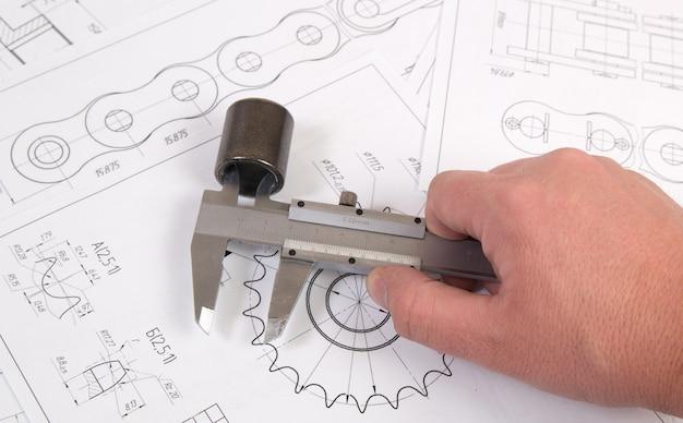 Dibujo técnico, pinza y cadena de rodillos de accionamiento. ingeniería, tecnología y metalmecánica. pinza de medida de detalle de cadena industrial.