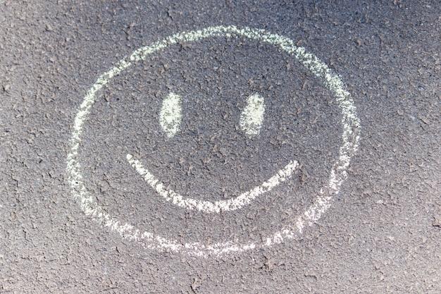 Dibujo de tiza del niño de una sonrisa sobre asfalto. buen día con buena luna.