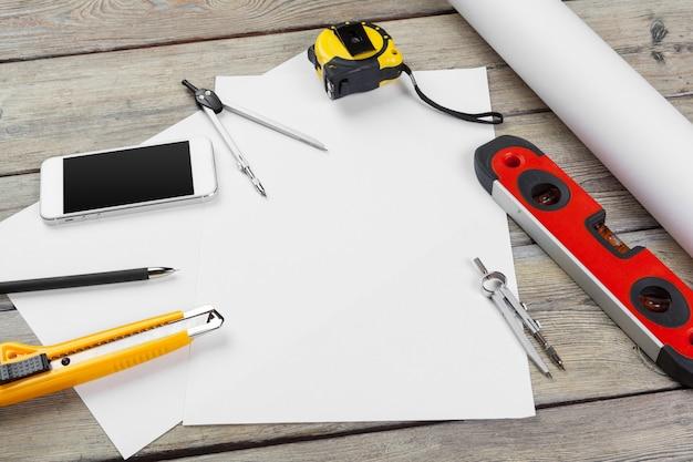 Dibujos arquitectónicos. instrumentos en la mesa de trabajo. hoja de papel en blanco