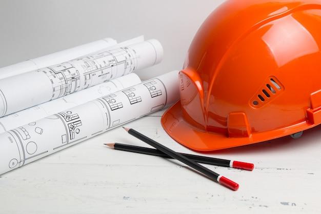 Dibujos de casa de ingeniería, casco, lápices y planos.