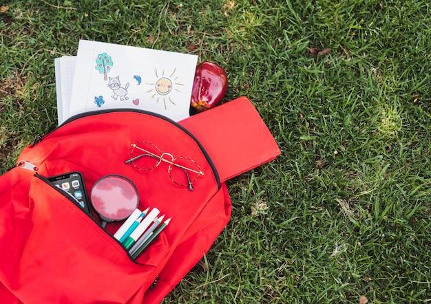 Dibujos cerca de mochila roja con papelería y teléfono inteligente.