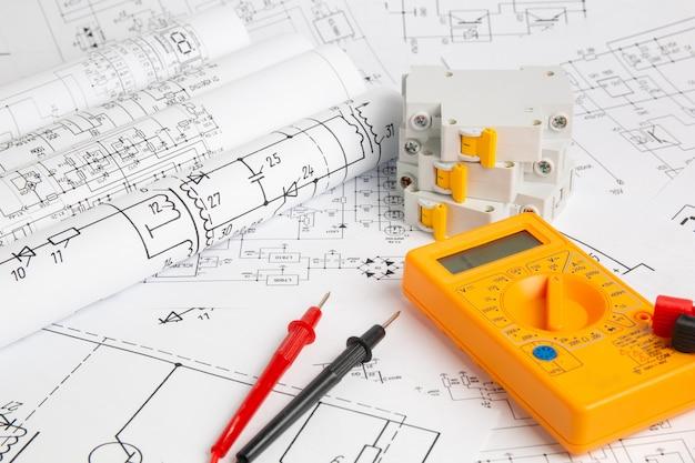 Dibujos impresos de circuitos eléctricos, multímetro digital y disyuntor eléctrico
