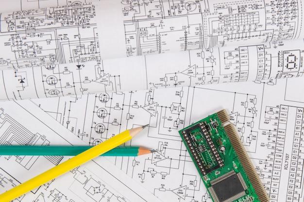 Dibujos impresos de circuitos eléctricos, tableros electrónicos y lápices.