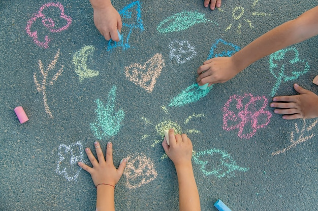 Dibujos infantiles sobre el asfalto con tiza.