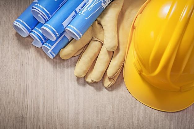 Dibujos de ingeniería azul edificio casco guantes de protección de cuero sobre tablero de madera.