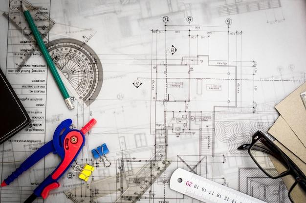 Dibujos de planificación de construcción sobre la mesa con lápices, regla y vasos sobre la mesa, efecto retro