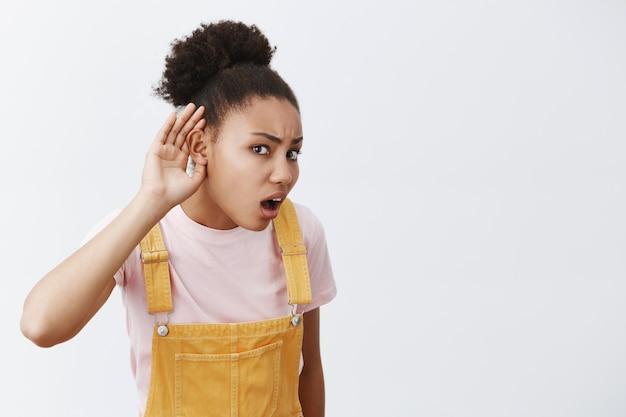 Dices lo que repites. retrato de mujer afroamericana intensamente confundida con el pelo recogido en un moño, sosteniendo la palma cerca de la oreja para escuchar mejor, pregunta mal sobre la pared gris