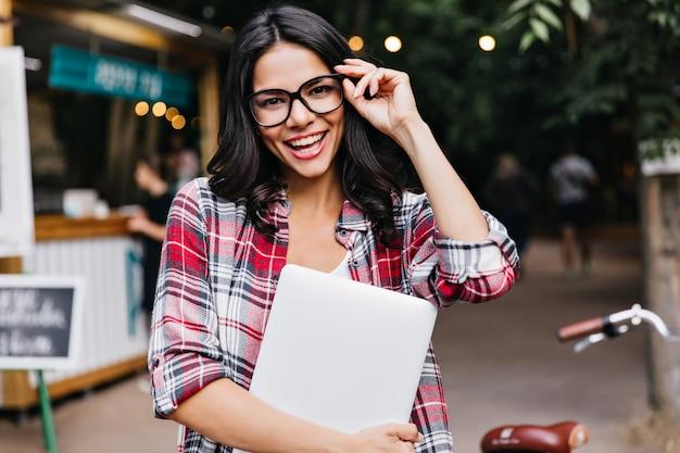 Dichosa chica de cabello oscuro con portátil tocando sus gafas. retrato al aire libre de freelancer latina feliz.