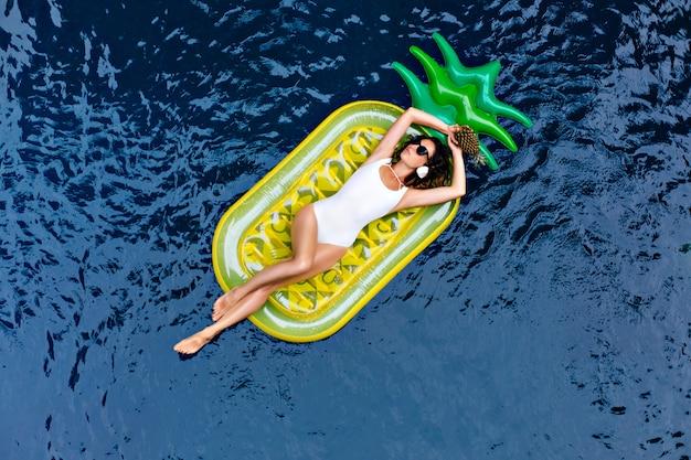 Dichosa chica morena pasar tiempo en el resort. foto exterior de feliz mujer blanca acostada sobre un colchón de piña brillante.