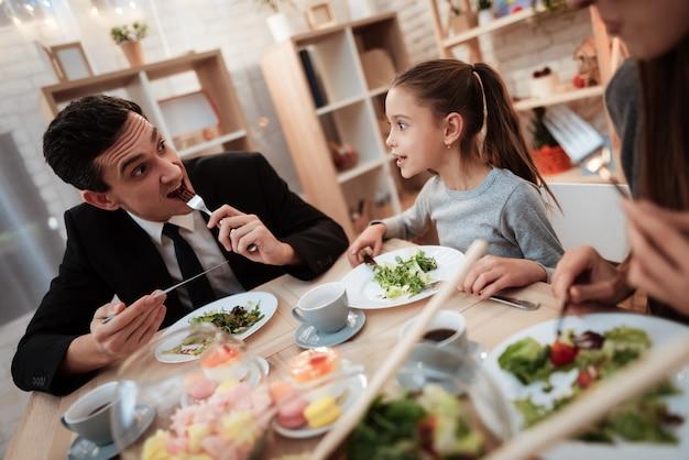 Dichosa familia comiendo platos en la mesa juntos.