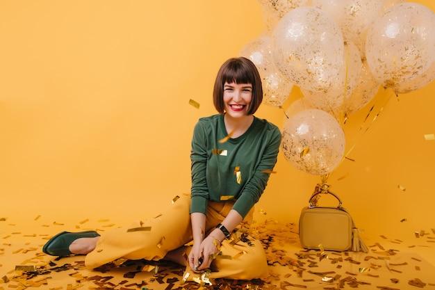 Dichosa niña blanca riendo y mirando confeti dorado. foto interior de modelo morena alegre divirtiéndose en la fiesta de cumpleaños.