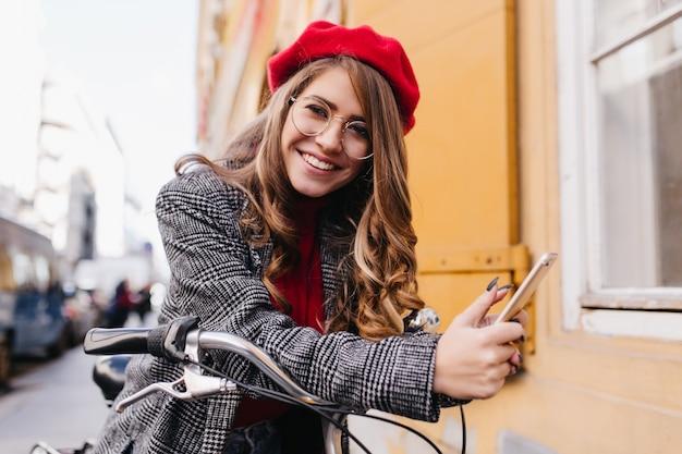 Dichosa niña caucásica lleva chaqueta de tweed leyendo un mensaje telefónico en el fondo de la ciudad