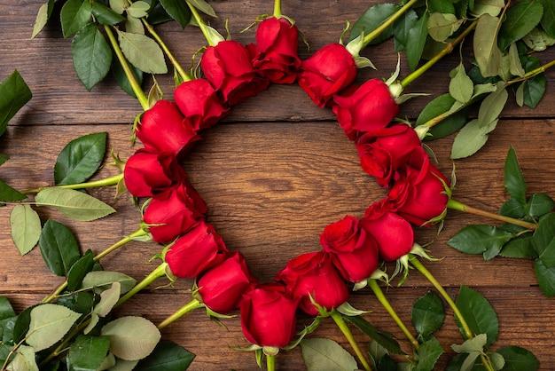 Dieciséis rosas rojas en la mesa de madera con espacio de copia de forma de marco