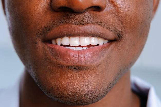 Dientes blancos sonríen hombre negro de cerca