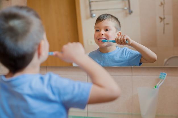 Dientes de cepillado felices del niño o del niño en cuarto de baño.