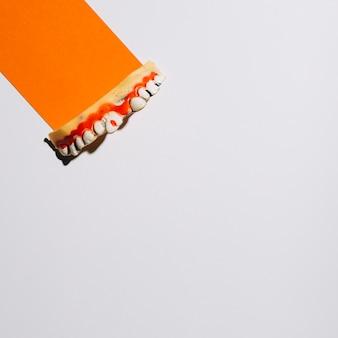 Dientes decorativos en una pieza de papel naranja