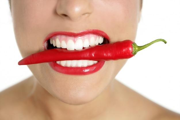 Dientes hermosos de la mujer que comen la pimienta roja