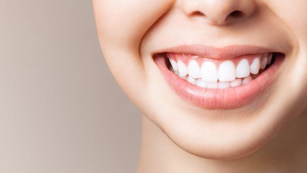 Los dientes sanos perfectos sonríen de una mujer joven. blanqueamiento dental. clínica dental paciente. la imagen simboliza la odontología del cuidado bucal, la estomatología. imagen de odontología.